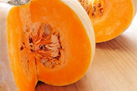 cucurbita: closeup of a cut pumpkin on a wooden surface