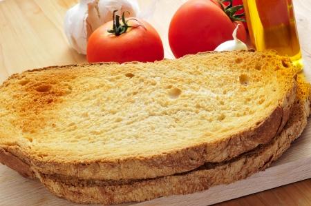 rebanadas de pan tostado y ajo, aceite de oliva y tomate, para preparar pan con tomate típico de Cataluña, España