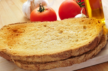 toasted bread slices, and garlic, olive oil and tomato, to prepare pa amb tomaquet typical of Catalonia, Spain photo