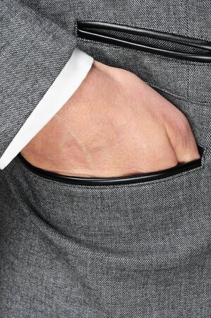 hand in pocket: detail of a man wearing a gray jacket suit