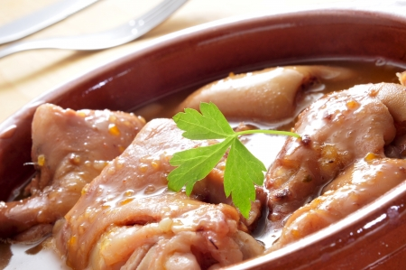 trotters: closeup of a earthenware casserole with manitas de cerdo, stewed pig feet typical of Spain Stock Photo