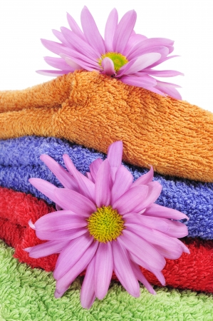 closeup of a pile of towels of different colors and some pink flowers on a white background photo
