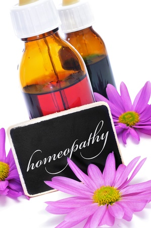 botanical remedy: some dropper bottles and a blackboard with the word homeopathy written on it and pink flowers Stock Photo