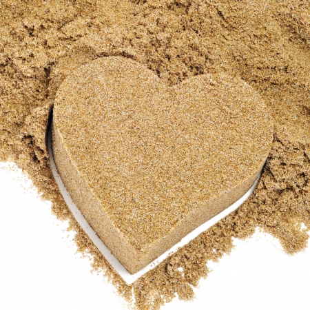 anniversary beach: a sand heart and a pile of sand on a white background