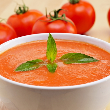 andalusian cuisine: closeup of a bowl with spanish gazpacho and some tomatoes Stock Photo