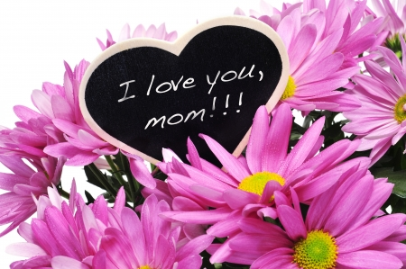 sentence I love you, mom written with chalk on a heart-shaped blackboard on a bouquet of pink chrysanthemums photo