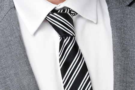 detail of a man wearing a gray jacket suit, white shirt and black and white striped tie photo