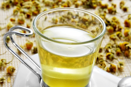 thirstiness: closeup of a glass cup with chamomile tea and a pile of dried chamomile flowers Stock Photo