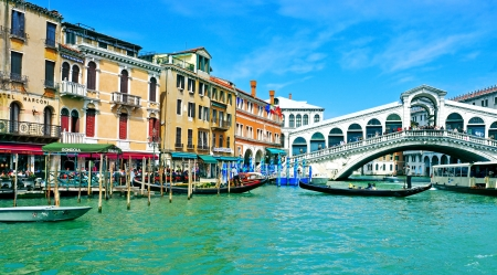 Venice, Italy - April 11, 2013: A view of the Grand Canal and Rialto Bridge in Venice, Italy. This main canal is 3800 meter long, 30?90 meters wide, with an average depth of five meters