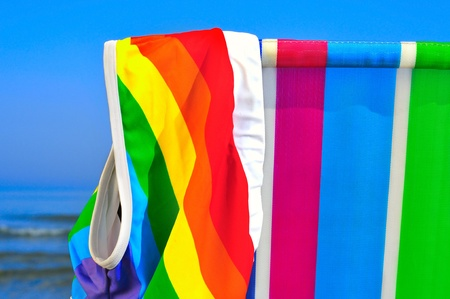nudism: a swimsuit patterned with the rainbow flag on a deck chair of different colors on the beach