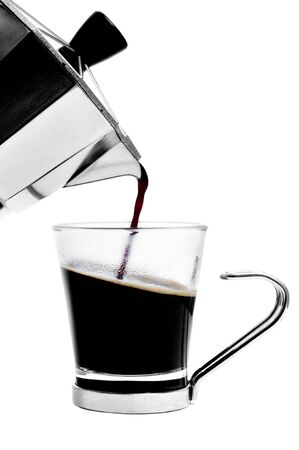 a cup with coffee served from a steel moka pot on a white background photo