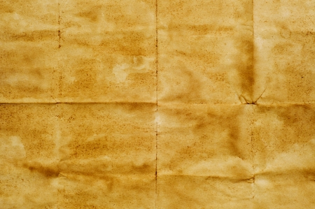paper folding: closeup of a yellowish old paper with folding marks