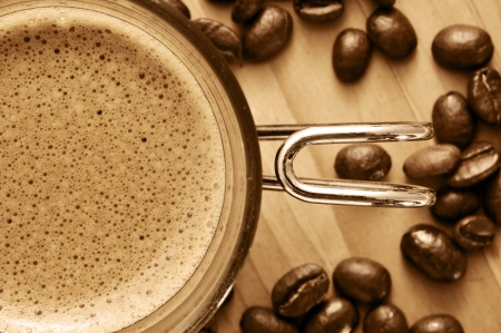 closeup of a cup of coffee and some coffee beans on a wooden table in sepia toning Stock fotó