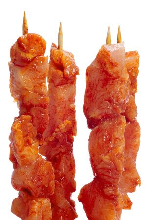 closeup of some raw spanish pinchos morunos, spiced chicken meat skewers, on a white background