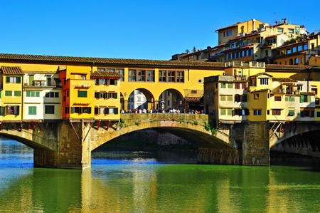 Florence, Italy - April 14, 2013: Ponte Vecchio and Arno River in Florence, Italy. This medieval bridge is one of the most visited landmarks in Florence and the most picturesque