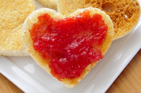 marmalade: closeup of a plate with heart-shaped toasts and strawberry jam