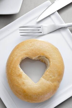 a plate with a plane bagel with a heart-shaped hole on a set table Stock Photo - 19365581