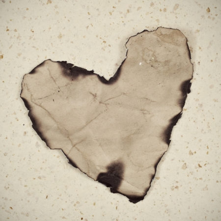 old paper heart with burnt edges on a textured background photo