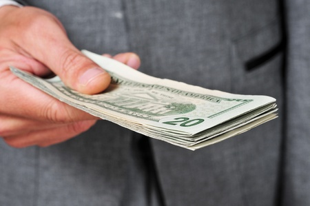 a man wearing a suit with a wad of dollars in his hand Stock Photo - 19500429