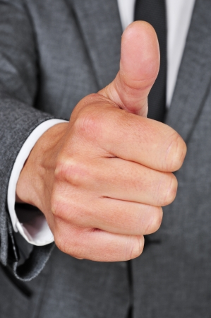a man wearing a suit making thumbs up sign photo