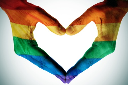 lesbianas: hombre manos pintadas como la bandera del arco iris que forman un corazón Foto de archivo