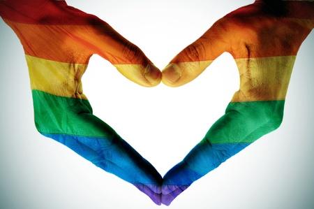 lesbienne: homme mains peintes que le drapeau arc-en formant un coeur Banque d'images