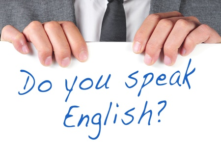 sentence: a man wearing a suit holding a signboard with the sentence do you speak english  written on it
