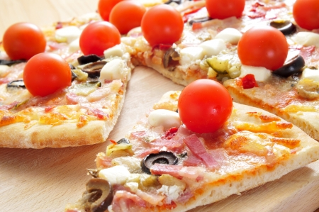 some slices of pizza with bacon, olives, cherry tomatoes, goat cheese, green pepper and eggplant photo