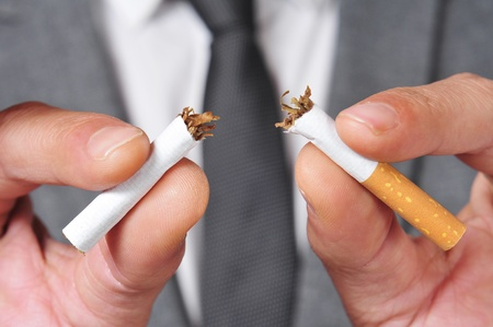 a man wearing a suit breaking a cigarette with his hands photo