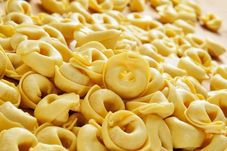 closeup of a pile of uncooked tortellini on a wooden table photo