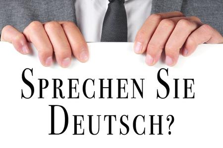 a man wearing a suit holding a signboard with the sentence sprechen sie deutsch  do you speak german  written in german on it Stock Photo - 19529078