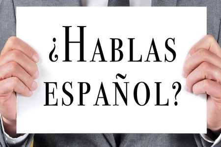 a man wearing a suit holding a signboard with the sentence hablas espanol  do you speak spanish  written in spanish on it photo