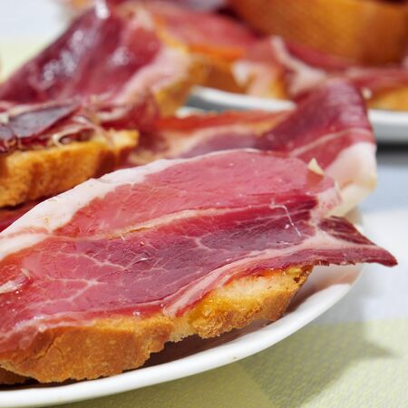 closeup of a some plates with spanish tapas of serrano ham served on sliced bread, on a set table of a restaurant photo