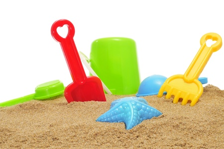 closeup of some beach toys, as a starfish-shaped sand mold, and shovels and rakes of different colors, on the sand of a beach or of a sandpit photo