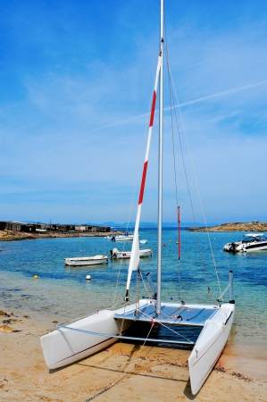cove: a sailboat and the Mediterranean Sea in Cala Sa Roqueta cove, in Formentera, Balearic Islands, Spain, and the typical slipways and fishermen huts, called barraques