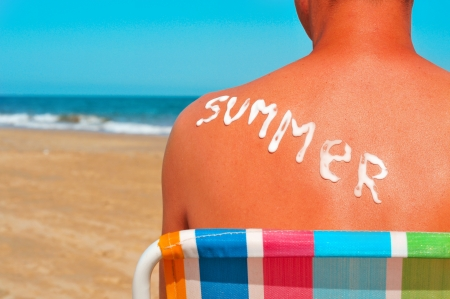 the word summer written with sunblock on the sunburnt back of a man who is sunbathing on the beach Stock Photo