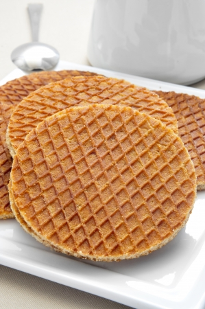 closeup of a plate with some stroopwafels, typical dutch cookies filled with syrup, on a table with a teapot Stock Photo - 20162780