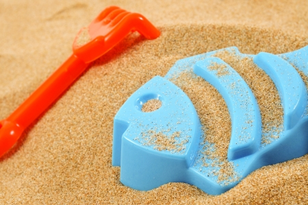 sand mold: a blue fish-shaped mold and an orange toy shovel on the sand Stock Photo