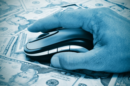 internet fraud: a hand man using a computer mouse on a background full of dollar banknotes, depicting the e-commerce concept or the internet fraud concept