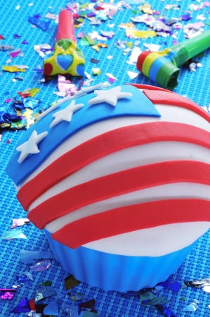a cupcake decorated with the american flag, in a blue background with confetti and party horns photo