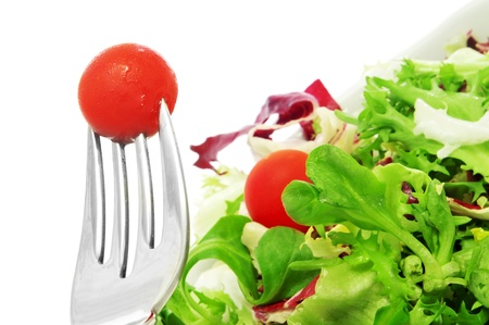 cornsalad: closeup of a fork with a cherry tomato and a plate of salad on a white background Stock Photo