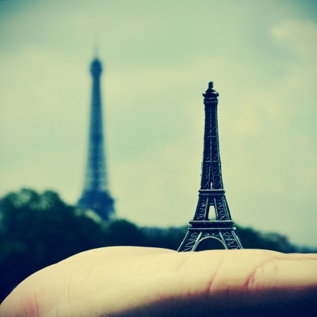 picture of someone holding a reproduction of the Eiffel Tower with the real Eiffel Tower in the background, in Paris, France, with a retro effect photo