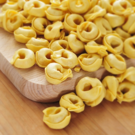 stuffed tortellini: a pile of uncooked tortellini on a table, ready to be boiled