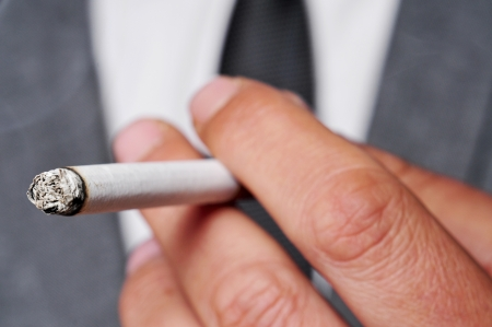 cancer drugs: a man wearing a suit smoking a cigarette
