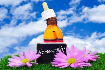 a dropper bottle and some purple flowers on the grass with a blackboard label with the word homeopathy written on it photo