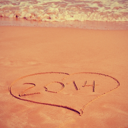 picture of a heart drawn on the sand of a beach with the number 2014, as the new year, written inside, with a retro effect photo