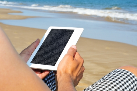 e reading: a man reading on an e-book on the beach Stock Photo