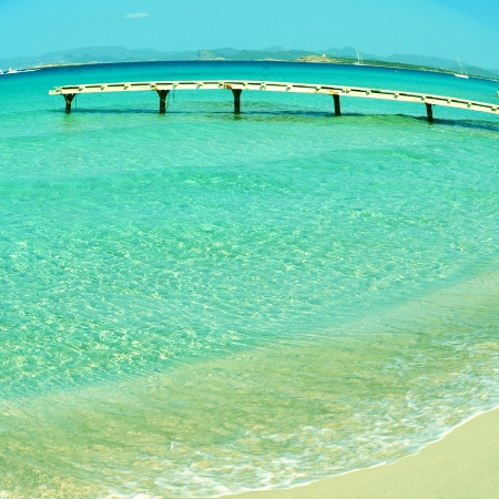 picture of a wooden pier in Ses Illetes Beach in Formentera, Balearic Islands, Spain, with a fisheye lens effect photo