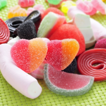 candy hearts: closeup of a pile of different candies on a green woven background