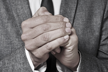 penny pinching: a man wearing a suit rubbing his hands